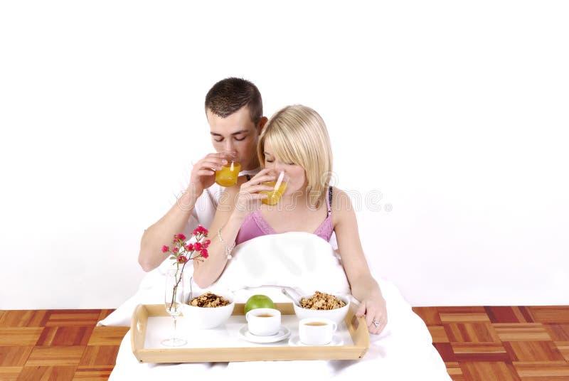 Junge Paare, die im Bett frühstücken lizenzfreies stockbild
