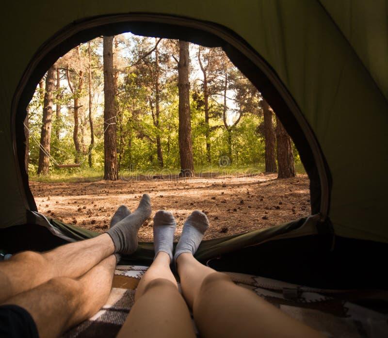 Junge Paare, die im Campingzelt stillstehen stockbilder