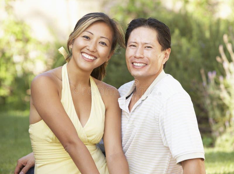 Junge Paare, die im Garten umarmen lizenzfreies stockbild