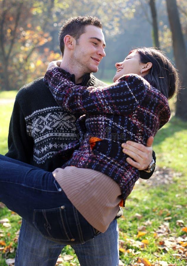 Junge Paare, die im Herbst im Freien umfassen stockbild