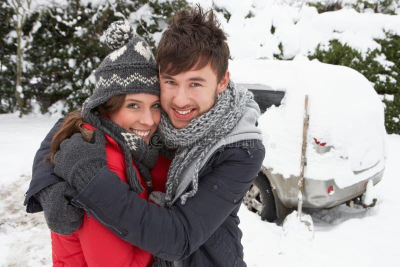Junge Paare, die im Schnee mit Auto umarmen stockfotos