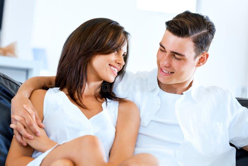 Junge Paare, die Kamera beim zu Hause sitzen betrachten stockbilder