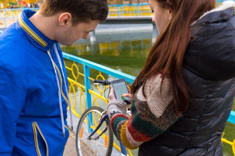 Junge Paare, die Karten-APP am Handy betrachten lizenzfreie stockbilder