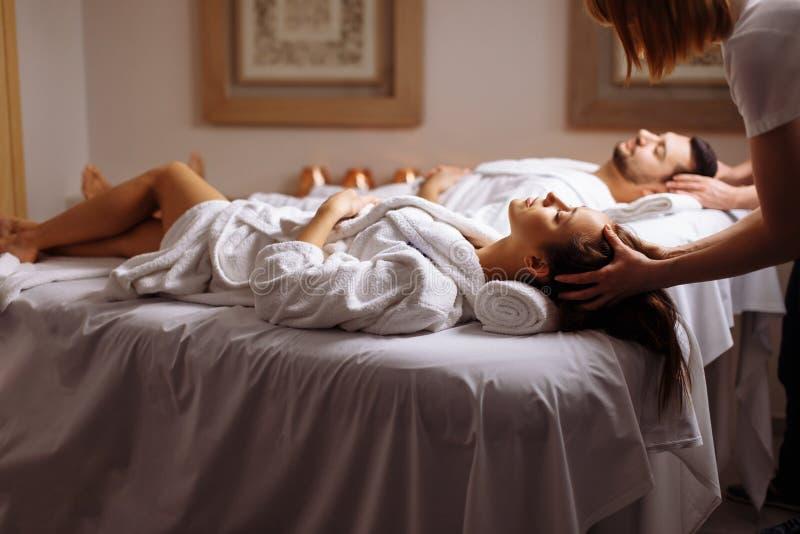 Junge Paare, die Kopfmassage am Schönheitsbadekurort empfangen lizenzfreies stockbild