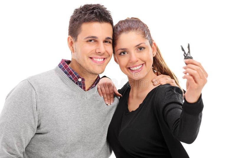 Junge Paare, die mit einem Paar Türschlüsseln aufwerfen lizenzfreies stockfoto