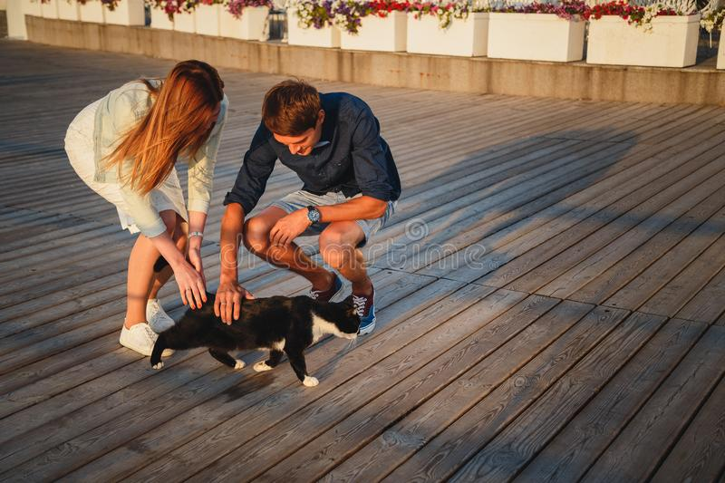 Junge Paare, die mit einer Katze draußen am Strand zur hölzernen PlattformSommerzeit spielen lizenzfreies stockbild