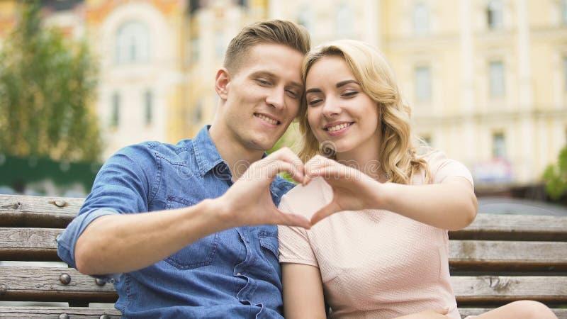 Junge Paare, die nah an einander setzend herauf das Finger-förmige Herz, datierend sitzen lizenzfreies stockbild
