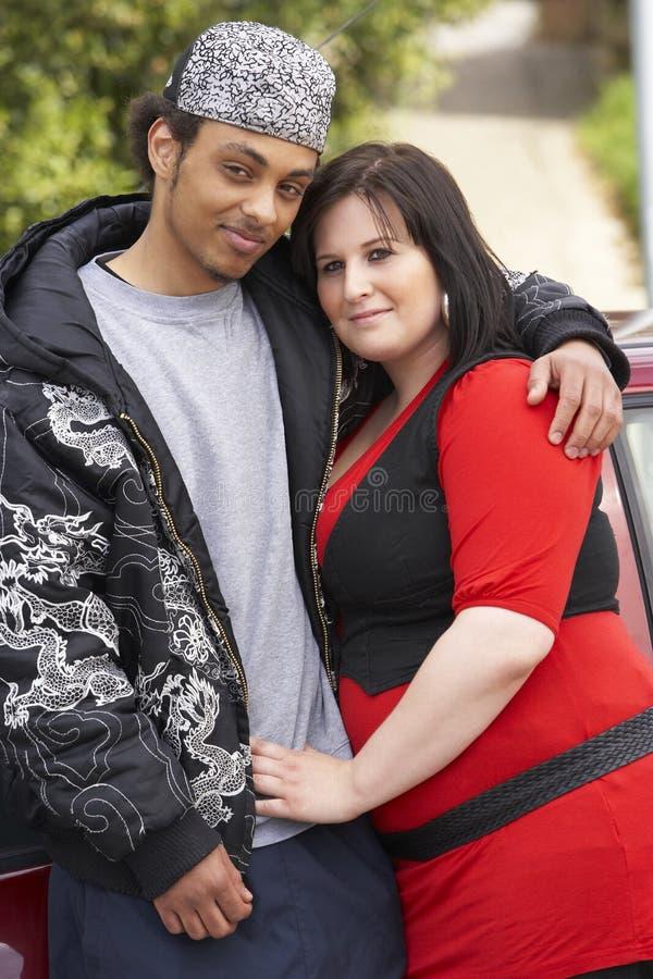 Junge Paare, die nahe bei Auto stehen stockbild