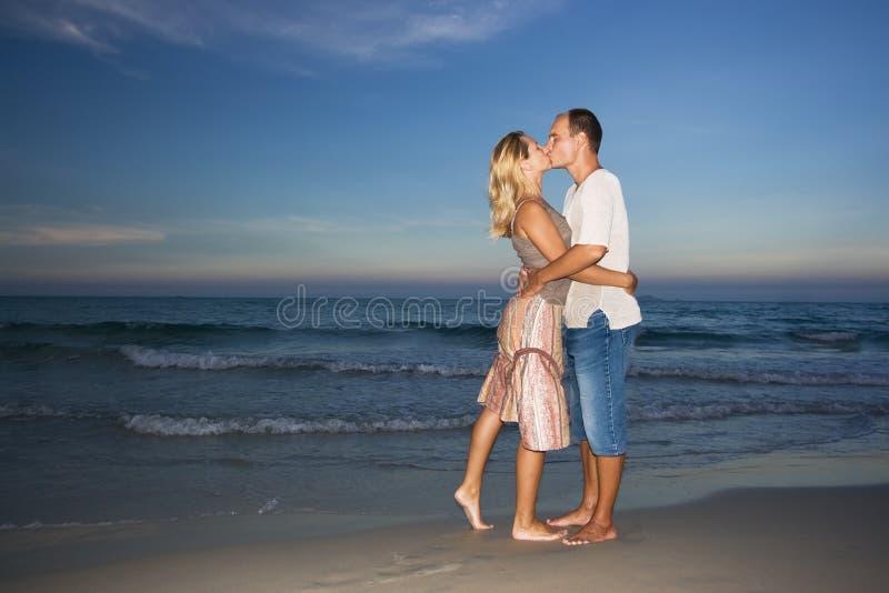 Junge Paare, die nahe dem Ozean küssen stockbild