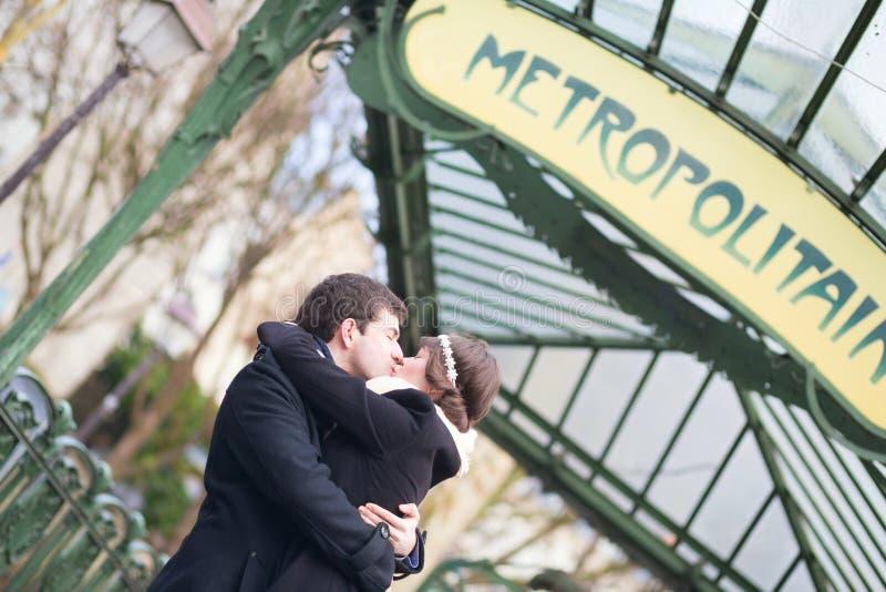 Junge Paare, die nahe Metrostation in Paris küssen stockbilder