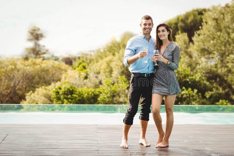 Junge Paare, die nahe Poolside genießen lizenzfreies stockfoto