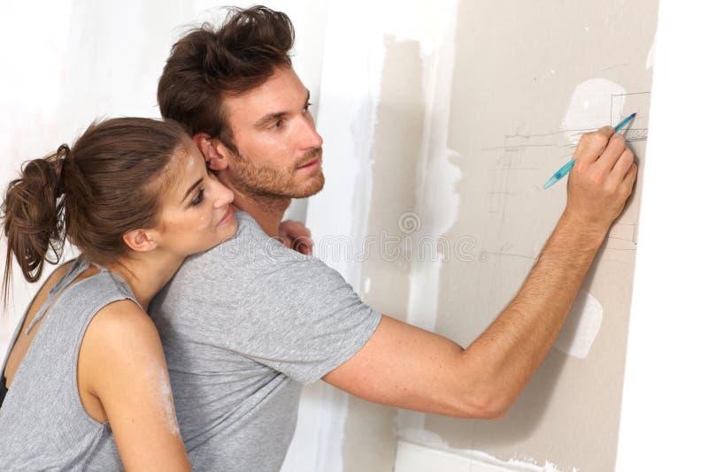 Junge Paare, die neues Haus planen stockbild