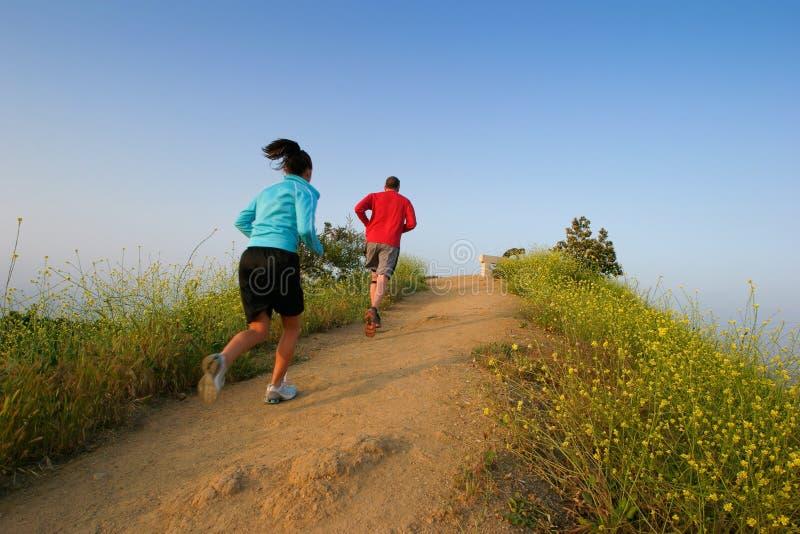 Junge Paare, die oben auf einen Hügel laufen. lizenzfreie stockfotografie