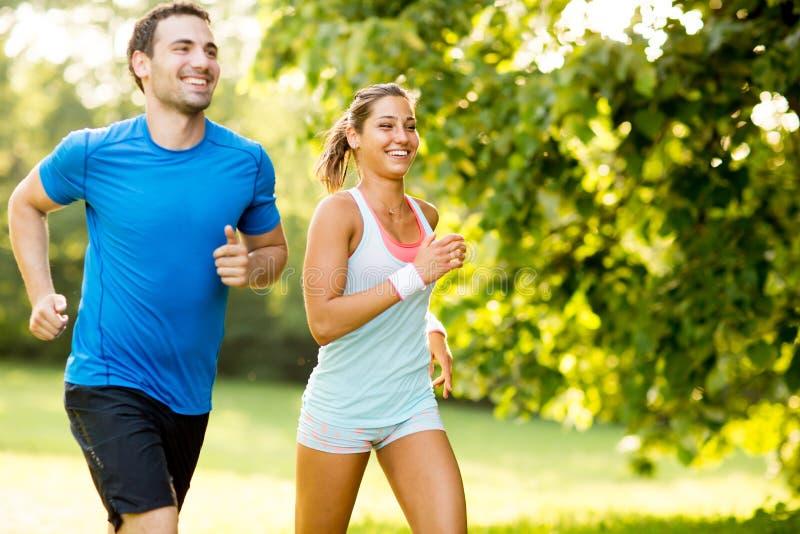 Junge Paare, die oben auf einen Hügel laufen lizenzfreie stockfotografie