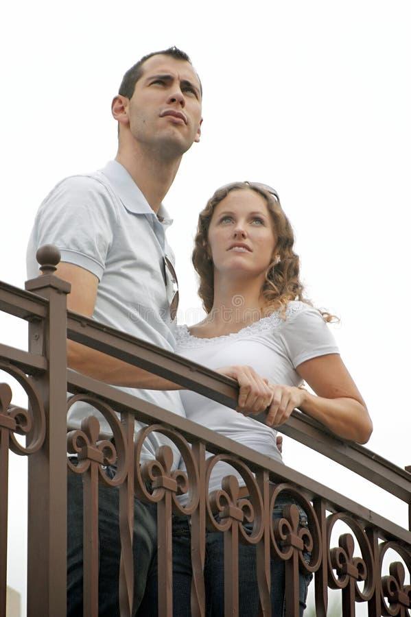 Junge Paare, die oben zum Himmel vom äußeren Ba schauen stockfoto