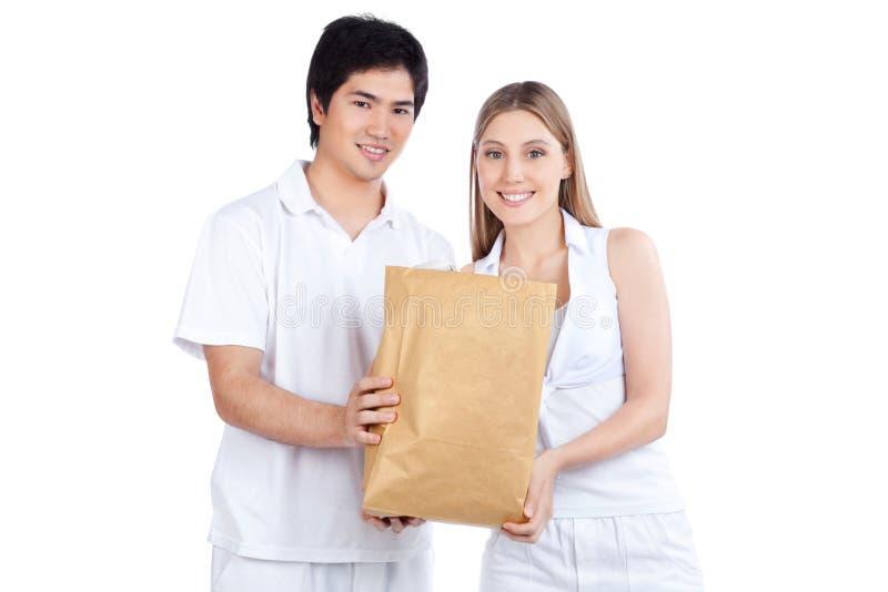 Junge Paare, die Papiertüte halten lizenzfreies stockfoto