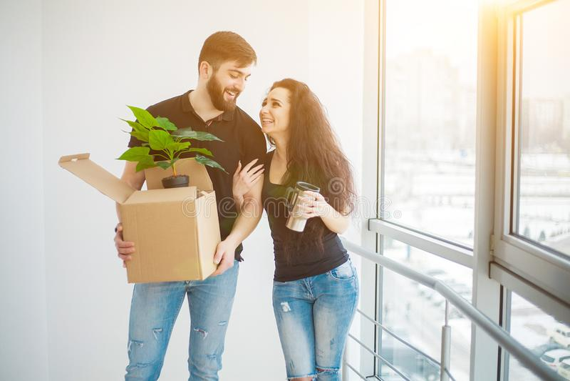 Junge Paare, die Pappschachteln am neuen Haus auspacken Bewegliches Haus lizenzfreie stockfotografie