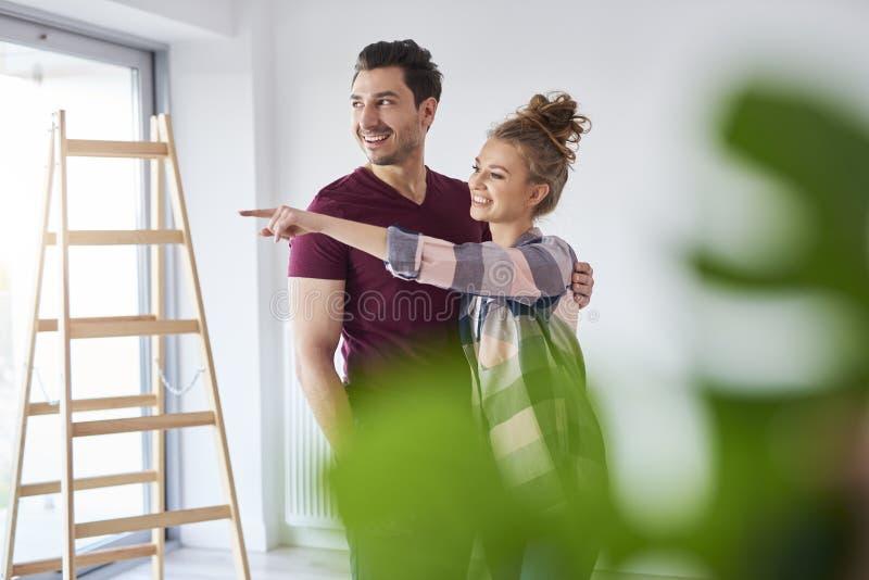 Junge Paare, die Pläne für Heimwerken machen lizenzfreies stockfoto