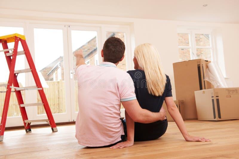 Junge Paare, die Pläne für neues Haus machen lizenzfreie stockfotos