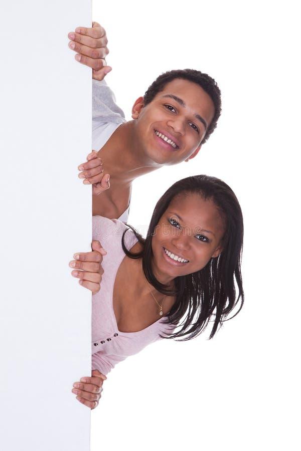 Junge Paare, die Plakat halten stockbild