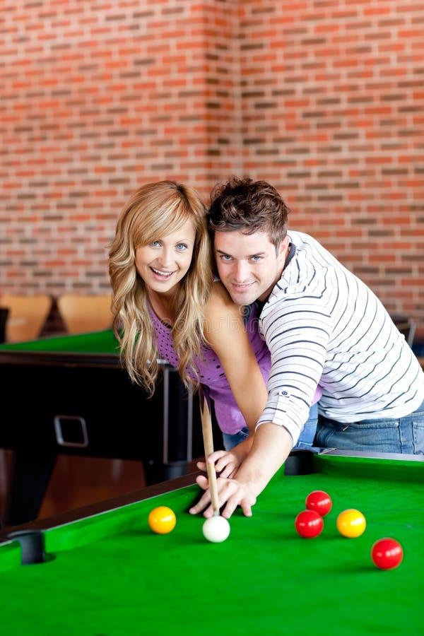 Junge Paare, die Pool spielen lizenzfreies stockfoto