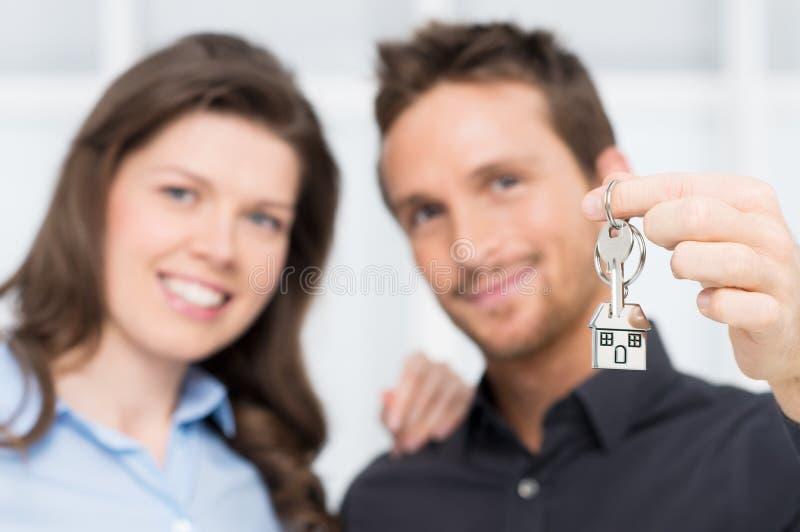 Junge Paare, die Schlüssel des neuen Hauses zeigen stockfotos