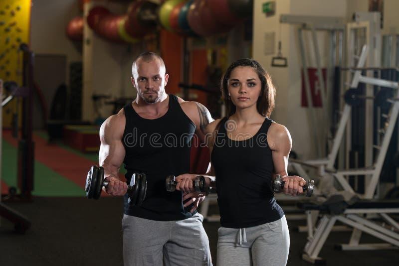 Junge Paare, die Schwergewichts- Übung für Bizeps tun lizenzfreie stockfotografie