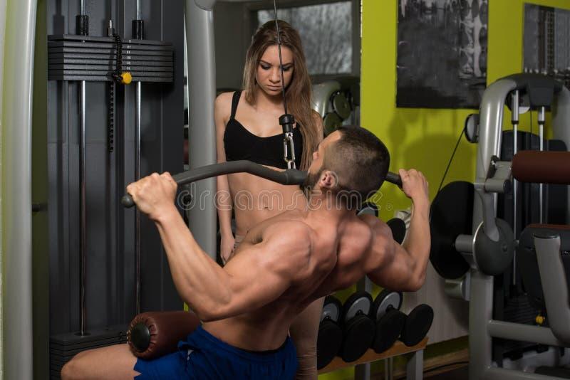 Junge Paare, die Schwergewichts- Übung für Rückseite tun stockbilder