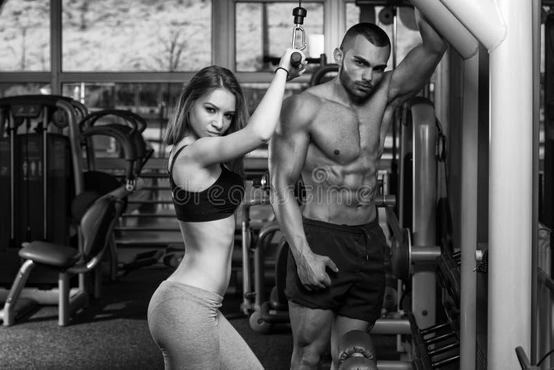 Junge Paare, die Schwergewichts- Übung für Trizeps tun lizenzfreie stockfotos
