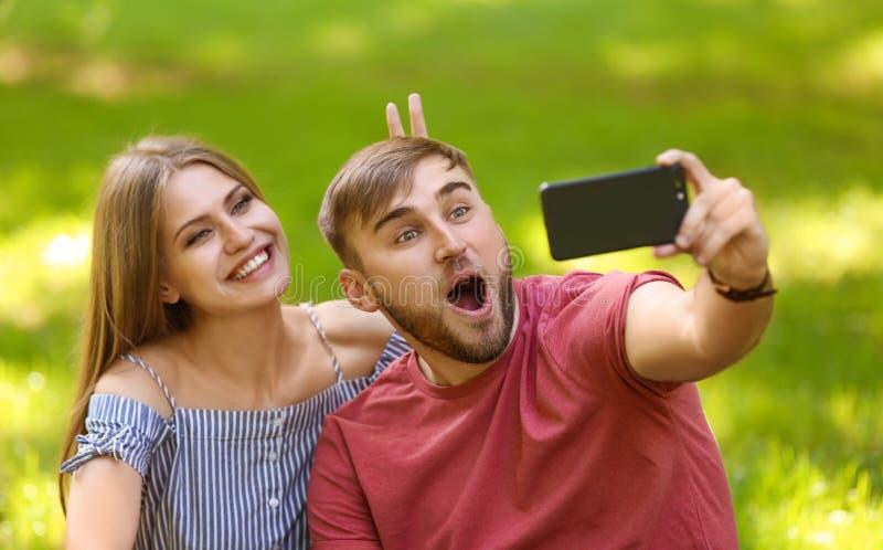 Junge Paare, die selfie auf grünem Gras im Park nehmen lizenzfreie stockfotos