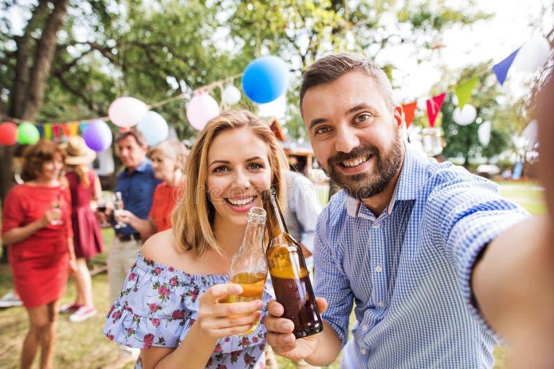 Junge Paare, die selfie an einer Partei draußen im Hinterhof, klirrende Flaschen nehmen stockbild