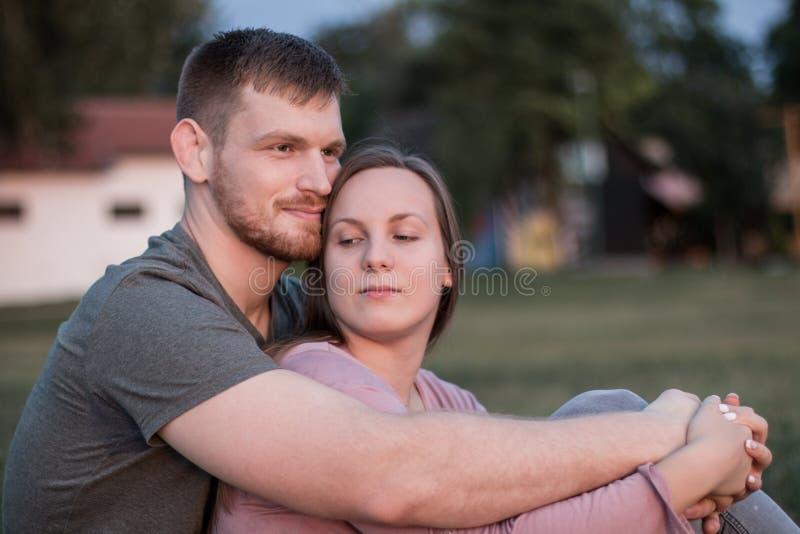 Junge Paare, die sich am Strand erholen und umarmen stockfotos