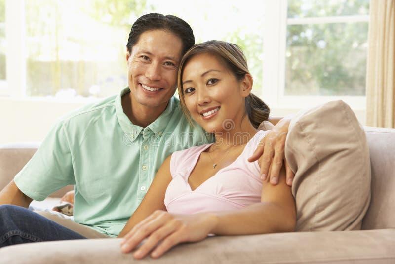 Junge Paare, die sich zu Hause auf Sofa entspannen lizenzfreie stockfotos