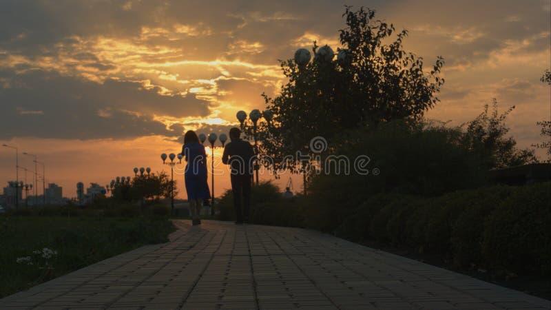 Junge Paare, die in Sonnenuntergang gehen plättchen stockbilder