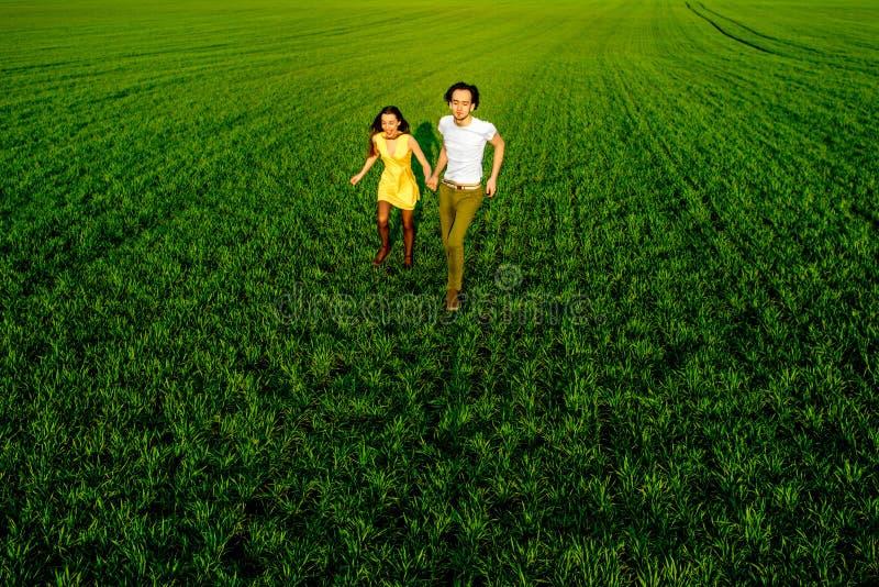 Junge Paare, die Spaß auf dem grünen Feld im Frühjahr oder summ haben stockfoto