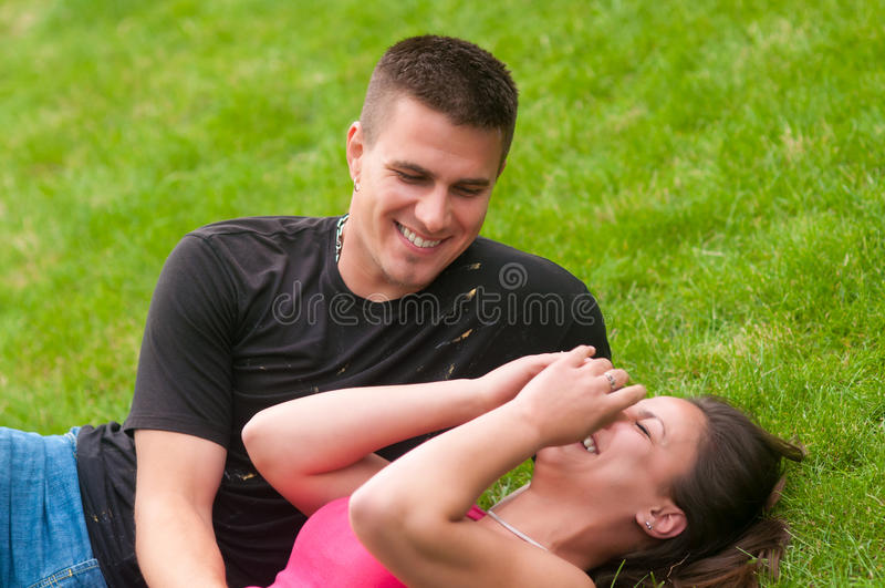 Junge Paare, die Spaß auf dem Gras haben stockbild