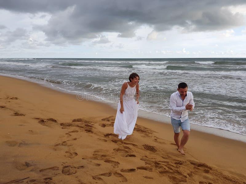 Junge Paare, die Spaß auf dem sandigen Strand von einem tropischen Ozean lachen und haben lizenzfreie stockfotografie