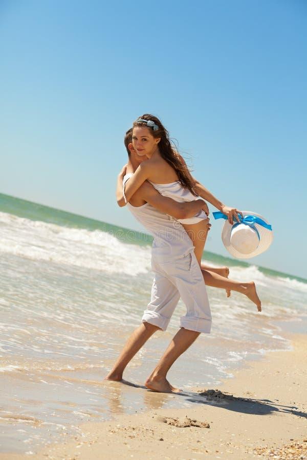 Junge Paare, die Spaß auf dem Strand haben lizenzfreie stockfotos