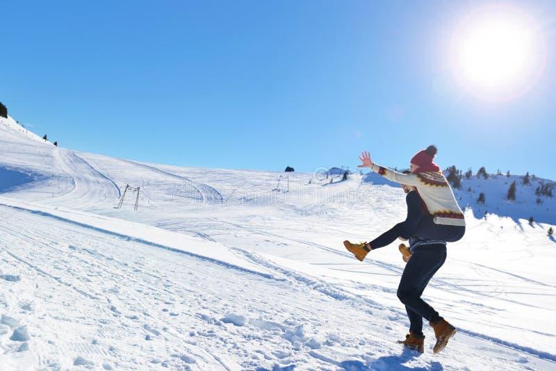 Junge Paare, die Spaß auf Schnee haben Glücklicher Mann am Berg, der seiner lächelnden Freundin Doppelpolfahrt gibt lizenzfreie stockfotografie