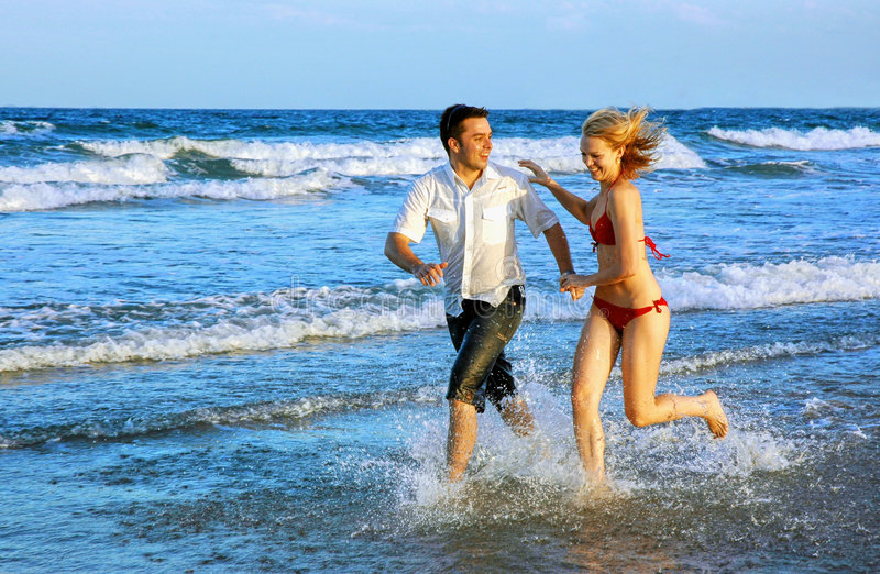 Junge Paare, die am Strand laufen stockfotografie