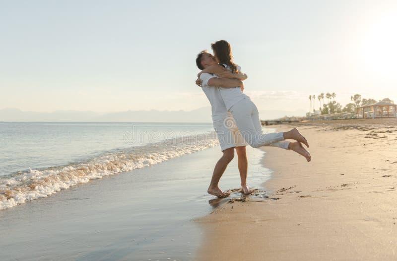 Junge Paare, die am Strand spielen lizenzfreie stockbilder