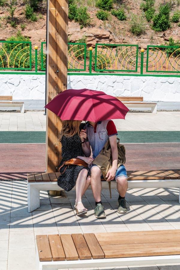 Junge Paare, die unter Regenschirm küssen stockfotos