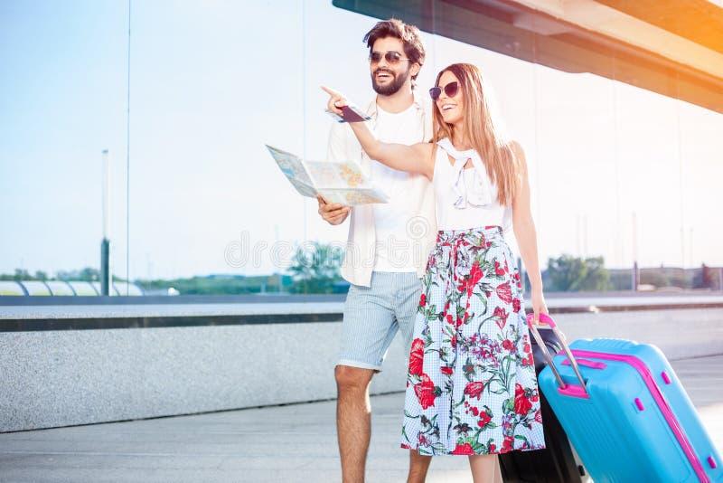 Junge Paare, die vor einem Flughafenabfertigungsgebäudegebäude, Koffer ziehend gehen stockbild