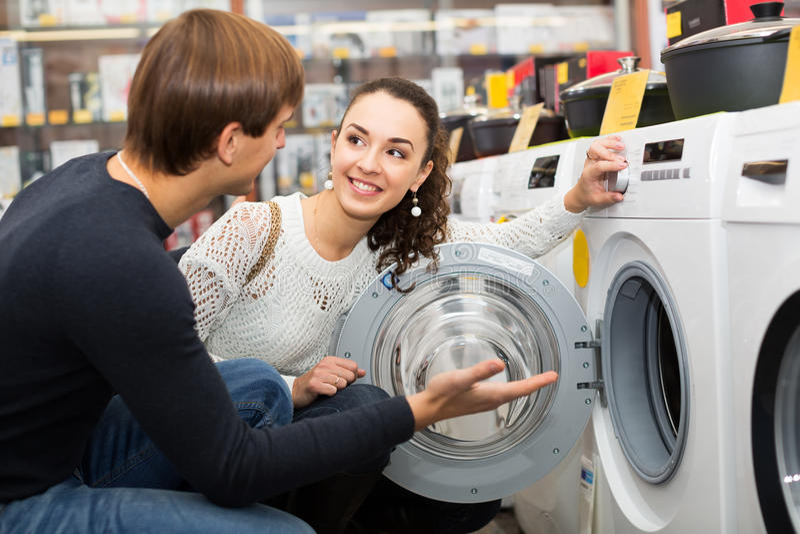 Junge Paare, die Waschmaschine wählen lizenzfreie stockfotos