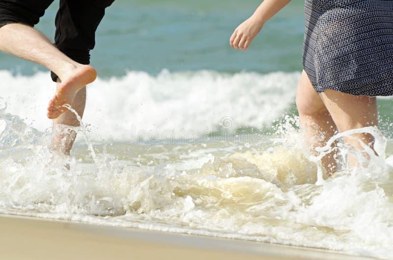 Junge Paare, die am Wasserrand von tropischem Ozean scherzen lizenzfreie stockfotografie