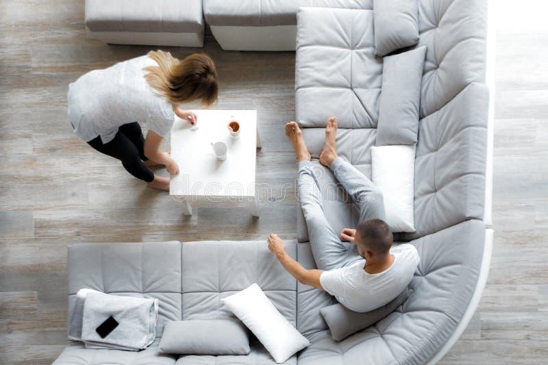 Junge Paare, die zu Hause auf Sofa stillstehen stockbilder