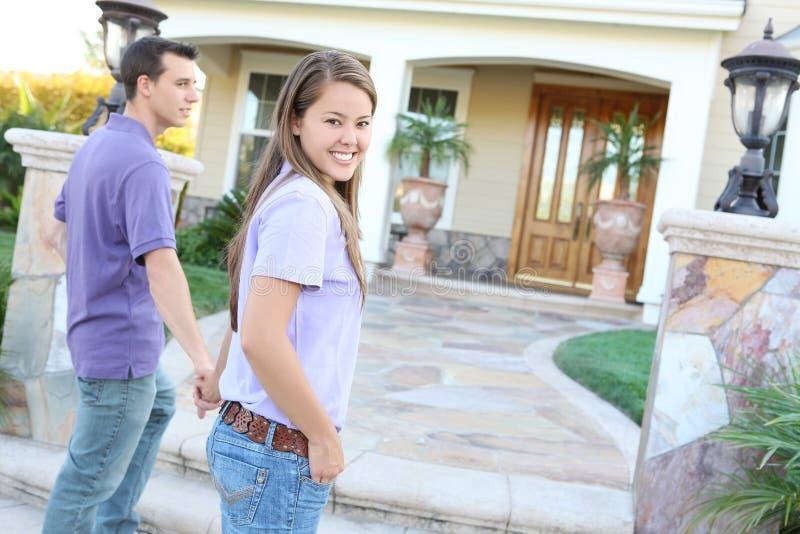 Junge Paare, die zu neuem Haus kommen stockfotos