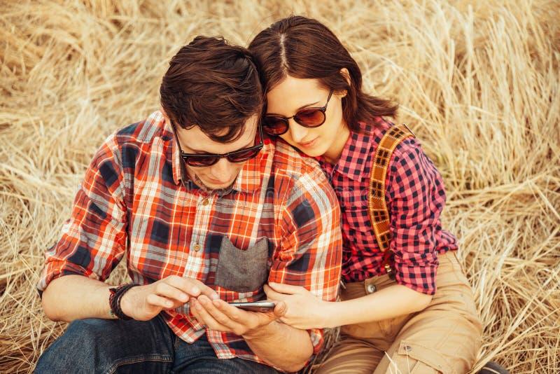 Junge Paare, die zum Handy aufpassen stockfotografie