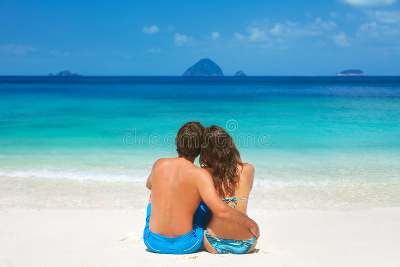 Junge Paare, die zusammen auf einem sandigen tropischen Strand sitzen stockbild
