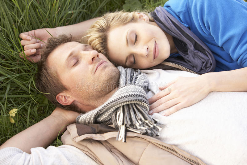 Junge Paare, die zusammen auf Gras liegen stockfotos